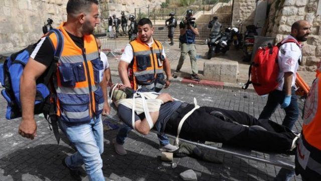 مسعفون فلسطينيون يحملون جريحا على نقالة عند باب الأسود في البلدة القديمة في القدس