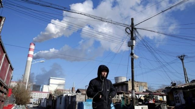 Rapaz andando em rua na China e, ao fundo, é possível ver fumaça saindo de fábrica