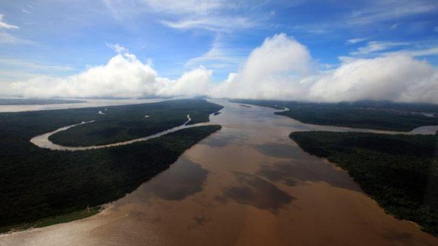Imagem aérea de um rio e uma área de floresta na amazônia