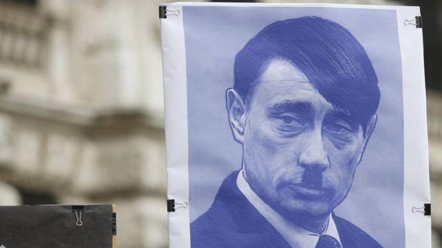 صورة من الأرشيف لمظاهرة في فيينا حمل فيها محتجون لافتة تصور بوتين في هيئة هتلر