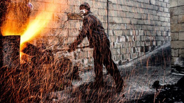 Күнөскана иштеткен фермер. Жашылча-жемиштер өскөн жайды ысык темпаратурада кармоо үчүн үчүн от жагып жатат.