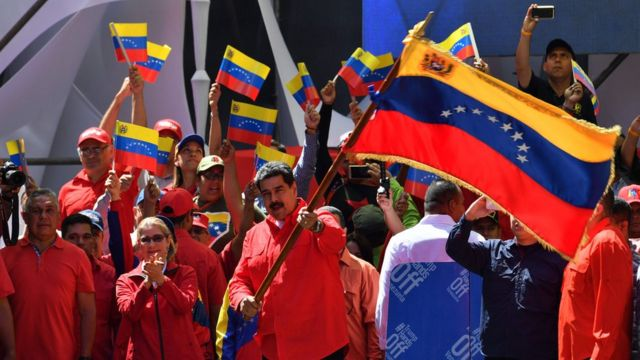 Venezuelan President Nicolas Maduro (C) waves the national flag during a pro-government march in Caracas, on February 23, 2019