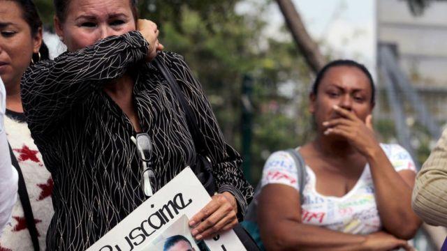 Una mujer familiar de un desaparecido de Jalisco se tapa la nariz con el brazo.