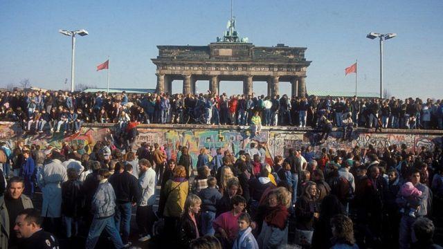 Gente sobre el muro delante de la puerta de Brandemburgo.
