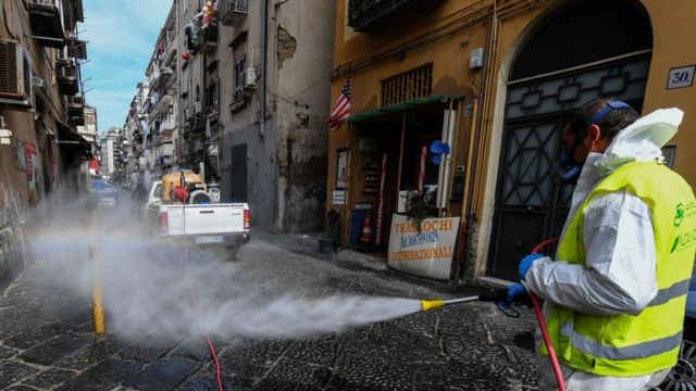 Hombre desinfecta una calle de Nápoles.