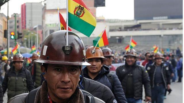 hombre boliviano con casco y bandera