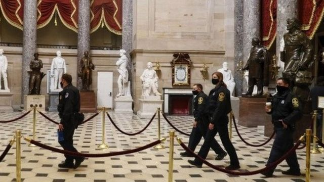 Police in the US Capitol building, the day after a deadly riot (7 Jan)