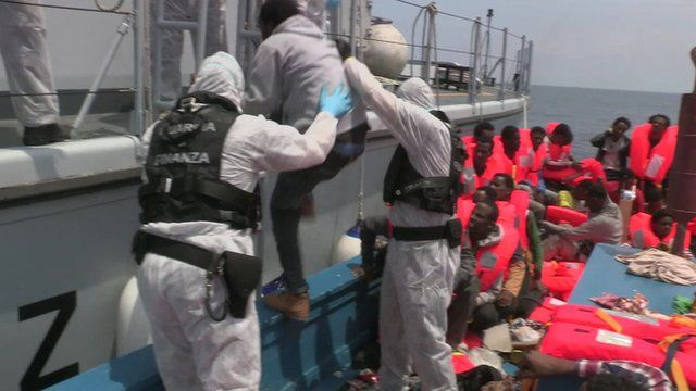 Migrant being hauled to safety