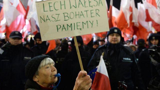 A demonstrator hold banner written: Lech Walesa is still our hero