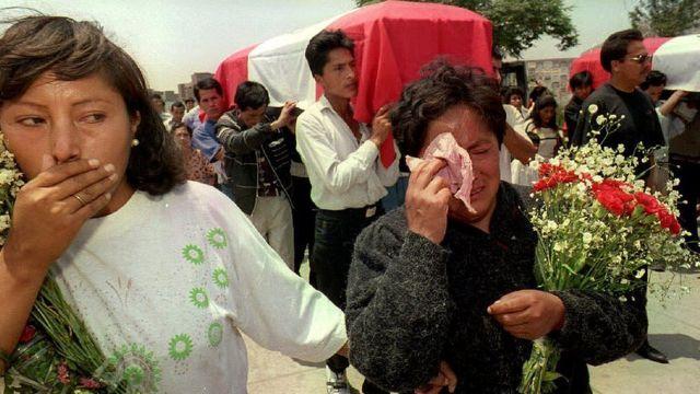 Mujeres lloran junto al ataúd de un policía víctima de Sendero.