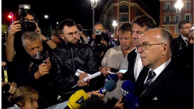 French Interior Minister Bernard Cazeneuve (right) talks to reporters