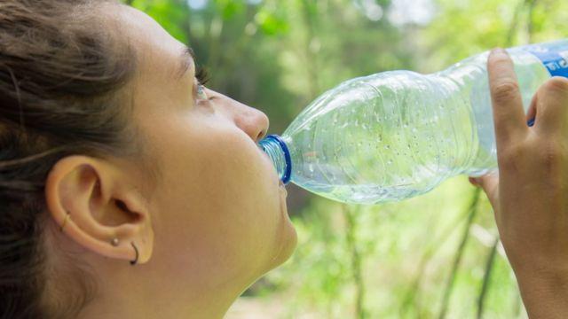 Mujer toma agua en botella de plástico.