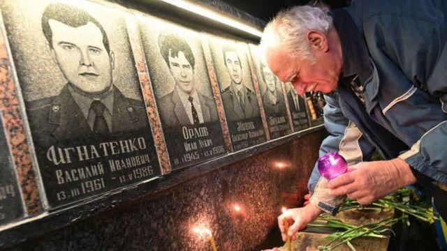 一位老人在切尔诺贝利核事故受害者像前点燃蜡烛