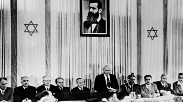 Le premier premier ministre d'Israël, David Ben-Gourion, sous un portrait de Theodor Herzl, fondateur du sionisme, déclare l'indépendance d'Israël.
