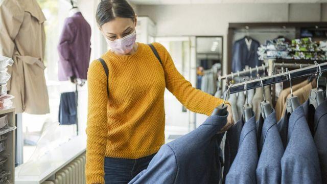 Mulher olhando roupa em loja