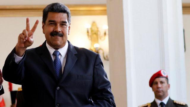 O presidente Nicolás Maduro sorri para a mídia depois de uma reunião, com um oficial do exército visível ao seu lado