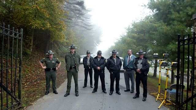 Law enforcement officers stand at the entrance to the Alderson Federal Prison Camp where Martha Stewart turned herself in October 8, 2004