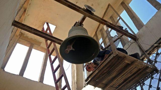 عامل يتفقد جرس كنيسة مار يوسف للكلدان في بغداد