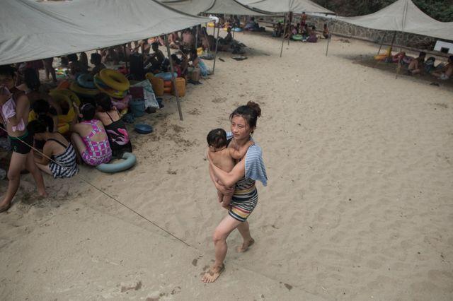 남포시 외곽의 한 해변가에서 아이를 안은 한 여성