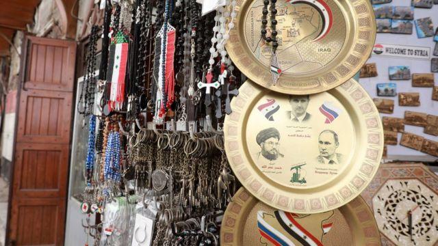 طبق في سوق سوري، نقشت عليه صور الأسد ونصر الله وبوتين