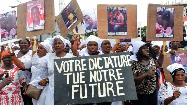"""Des femmes guinéennes tiennent des pancartes lisant """"Votre dictature tue notre avenir"""" alors qu'elles protestent contre les assassinats de manifestants et le troisième mandat du président guinéen Alpha Condé, exigeant également la libération des personnes arrêtées à Conakry le 23 octobre 2019. - Des centaines de femmes opposées à un troisième mandat du président guinéen Alpha Condé ont défilé mercredi à Conakry, au lendemain de la condamnation des principaux initiateurs des manifestations qui secouent la Guinée depuis une semaine et ont fait une dizaine de victimes."""