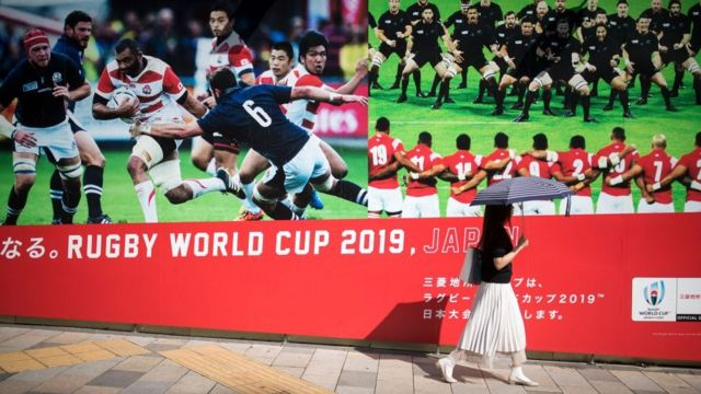 A commuter walks past posters advertising the Japan 2019 Rugby World Cup in the Tokyo district of Aoyama