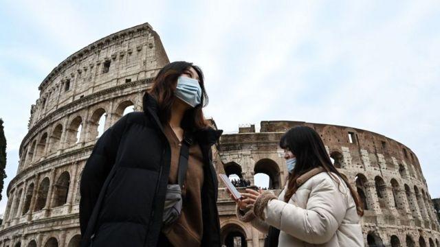 Personas con mascarillas frente al coliseo romano.