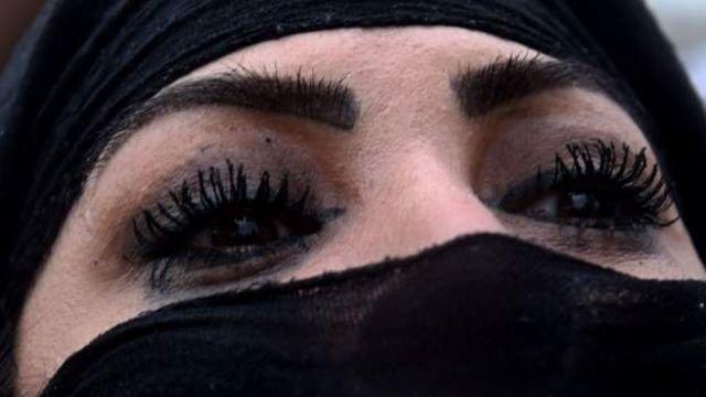Mujer con los ojos pintados y burka.