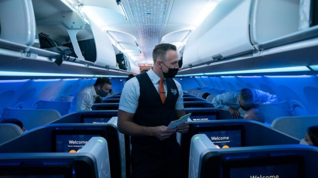 A flight attendant assists a passenger before a JetBlue flight to London at JFK International Airport in the Queens borough of New York City, New York, U.S., August 11, 2021.