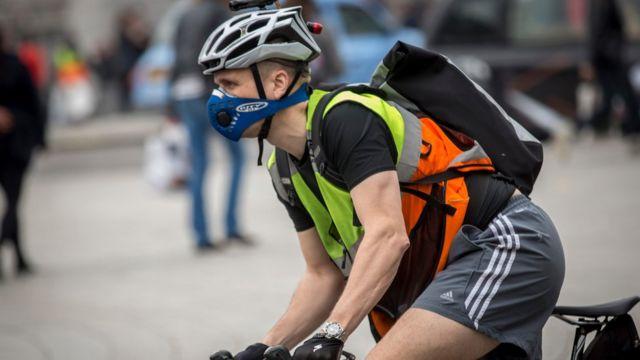 Un ciclista con la cara cubierta con una máscara que filtra el aire
