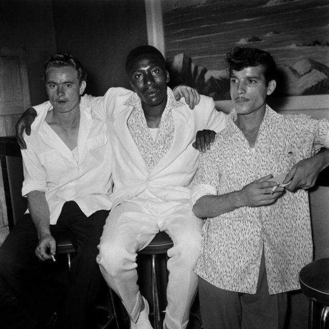 Trois hommes vêtus de chemises amples, cigarettes en main, près d'un bar.