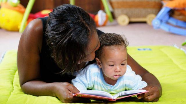 Madre leyendo un libro con su hija pequeña.
