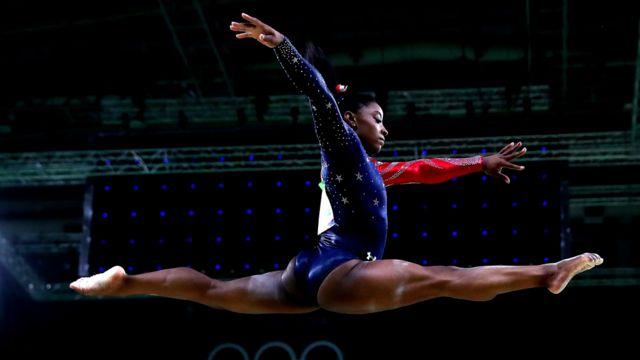 Simone Biles en el aire en una rutina de gimnasia olímpica en Río