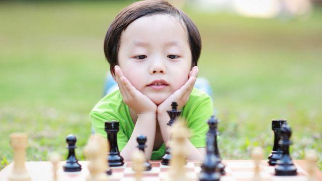 Imagem mostra criança jogando xadrez