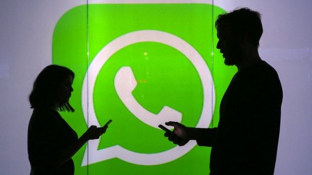 Dos personas sostienen sus celulares ante un cartel con el logotipo de WhatsApp.