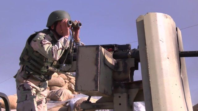 A Peshmerga figher on a gun emplacement