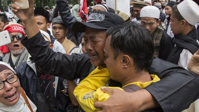 Seorang anggota kelompok anti-Ahok mengenakan topi dengan lambang bendera Hizbut Tahrir Indonesia, yang akan dibubarkan oleh pemerintah.