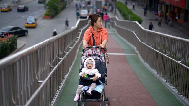 A woman pushes a baby carriage on an overpass in Beijing.
