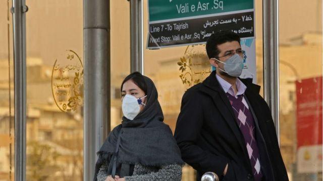 Người dân ở thủ đô Tehran, Iran đeo khẩu trang tại một bến xe buýt. Iran đang có tranh cãi về số người tử vong do dịch Covid-19