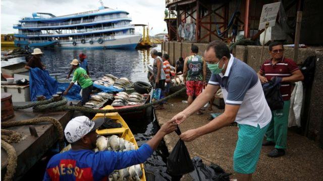 Homem compra peixe no porto em Manaus