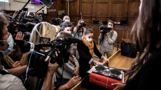 Valerie Bacot (de lenço amarelo no pescoço) chega ao tribunal, cercada por familiares e jornalistas