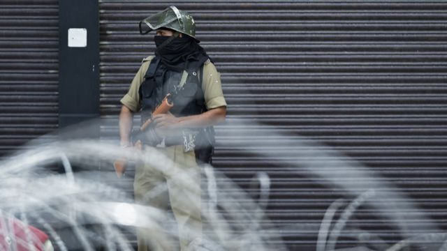 A security personnel stands guard on a street in Srinagar on August 28, 2019. - The Himalayan valley is under a strict lockdown -- with movement restricted and phone and internet services cut since August 5