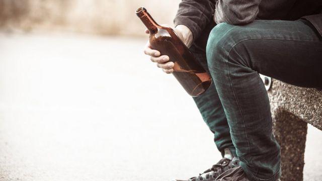 Hombre con una botella de alcohol