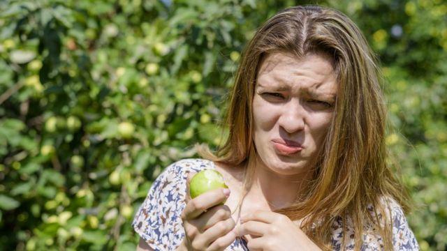 Una mujer asqueada tras comer una manzana.