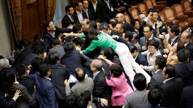 特別委の採決前、委員長席で押し合う与野党議員(17日)