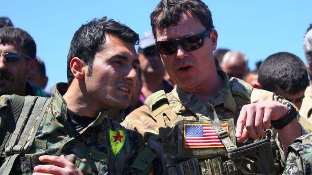 Un oficial estadounidense junto a un miembro de las YPG.