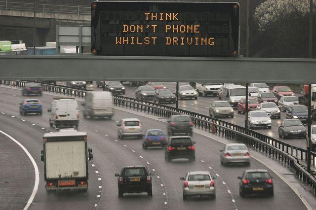 Растяжка над шоссе, предупреждающая водителей не пользоваться мобильными