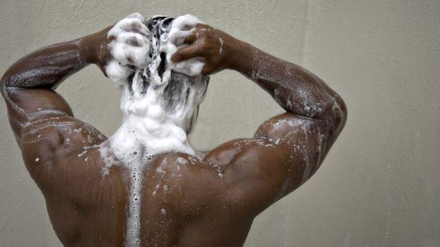 Homem lavando o cabelo com shampoo
