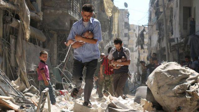Hombres llevan bebés a través de los escombros de edificios destruidos en un ataque aéreo del gobierno en Alepo, Siria