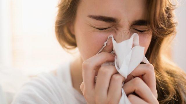 mulher limpando o nariz